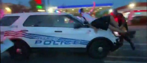 Detroit Police Car Drives Through Swarming Mob as Protesters Cling to Hood (Video)